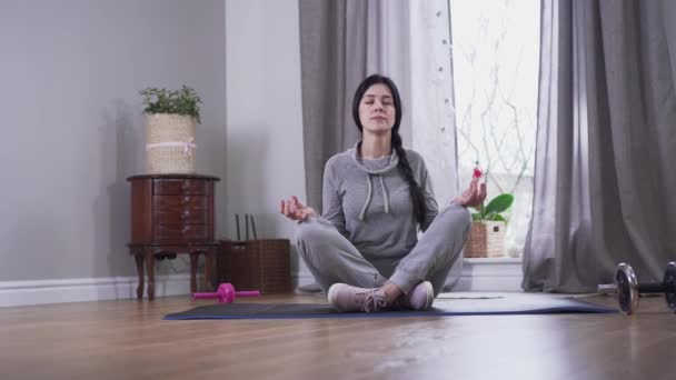 Camera approaching to confident brunette Caucasian woman meditating at home. Young woman sitting on yoga mat with eyes closed and crossed legs. Tranquility, lifestyle, relaxation.