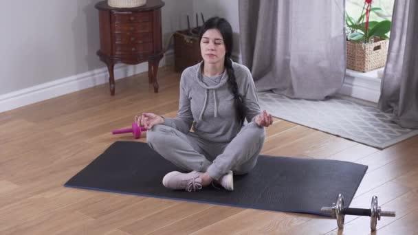 Pohled shora na mladou brunetku bělošku cvičící jógu v interiéru. Sebevědomá uvolněná žena meditující doma. Odpočinek, klid, životní styl.