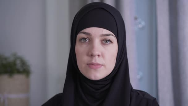 Close-up portrait of young beautiful Muslim woman in traditional black hijab. Charming lady looking at camera. Beauty, style, culture, lifestyle.