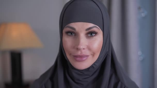 Close-up portrait of modern-looking woman with grey eyes in hijab. Young confident lady looking at camera and smiling. Lifestyle, culture, beauty.