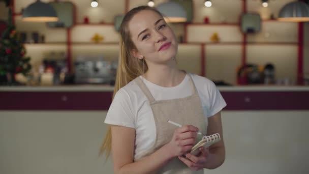 Porträt einer kaukasischen Kellnerin, die in die Kamera blickt und lächelt. junge Frau in Schürze, die mit Notizbuch und Stift im Café steht. Lebensstil, Beruf, Servicepersonal.
