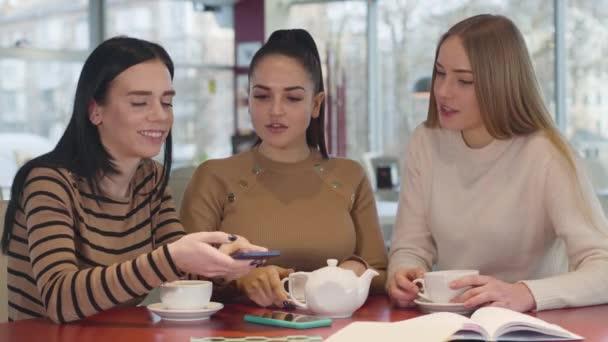 Detailní záběr tří bělošských přítelkyň, jak se dívají na obrazovku chytrého telefonu v restauraci a mluví. Mladé ženy drbaly u stolu v kavárně. Pověsti, životní styl, ženské přátelství.