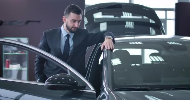 Mladý bruneta běloch stojí vedle nového černého auta s otevřenými dveřmi v prodejně. Úspěšný pohledný obchodník hledící do kamery a usmívající se. Cinema 4k Prores Hq.