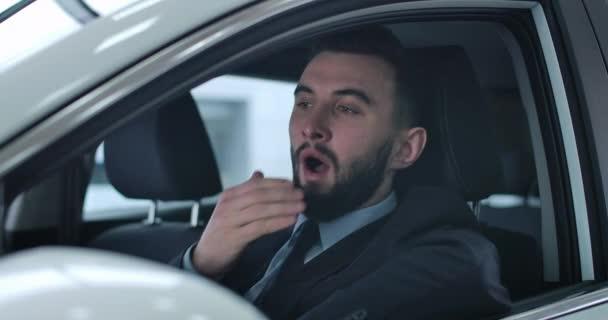 Nahaufnahme Porträt eines müden gutaussehenden kaukasischen Mannes, der auf dem Fahrersitz sitzt und gähnt. Erschöpfter privater Chauffeur oder Taxifahrer, der auf Kunden oder Chef wartet. kino 4k prores hq.