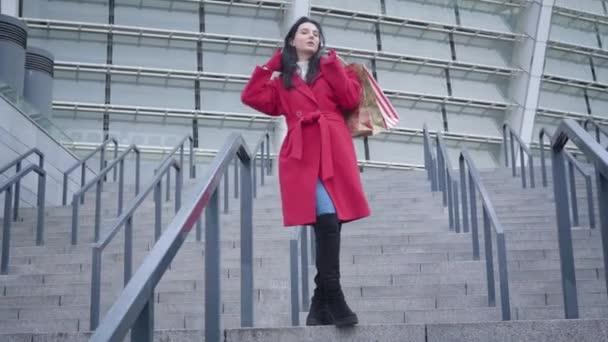 Spodní pohled na mladou stylovou bělošku stojící venku na schodech a dívající se do kamery. Portrét elegantní dámy pózující ve městě s nákupními taškami. Elegance, životní styl, shopaholismus.
