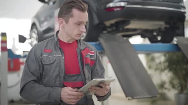 Portrait of concentrated Caucasian man using tablet and looking back at car in repair shop. Professional male auto mechanic working in auto service station. Industry, insurance, maintenance.