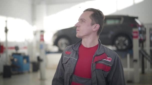 Young male auto mechanic looking around in repair shop and thinking. Portrait of Caucasian maintenance engineer in workrobe at workplace. Automobile industry, car insurance, tuning, repairing.