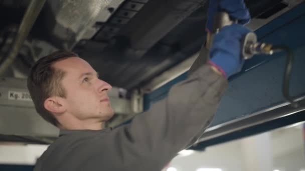 Közelkép oldalnézetben magabiztos kaukázusi férfi munkaruhában, professzionális felszereléssel az autó karbantartásához. Fiatal férfi autószerelő, a jármű meghibásodását javítja. Szervizállomás, javítóműhely.