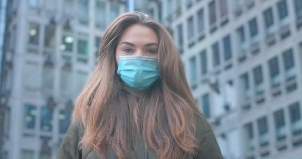 Portrait of beautiful Caucasian woman with grey eyes wearing protective mask in city. Young girl standing at the background of buildings. Coronavirus, covid-19, global problem. Cinema 4k ProRes HQ.