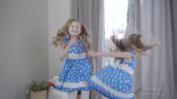 Joyful pretty Caucasian girls in elegant blue dotted dresses jumping and spinning at home. Portrait of cheerful happy twins having fun. Leisure, family, resting.