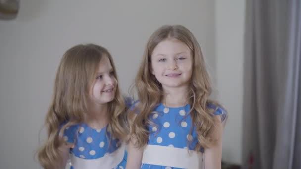 Veselá bělošská brunetka, dívající se na dvojče, pózující v popředí a kladoucí prsty jako rohy na hlavu sourozence. Životní styl, volný čas, radost, žertování.