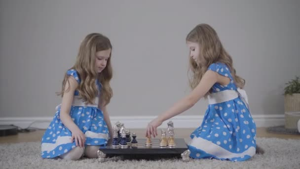 Side view of two concentrated Caucasian sisters playing chess. Portrait of focused twins sitting in front of each other with chessboard between. Hobby, leisure, lifestyle, intelligence.