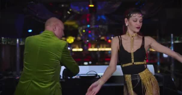 Zadní pohled na aktivní starý kavkazský Dj mixování hudby pomocí ovladače jako mladý jít tanečnice v svůdné šaty tanec na jevišti vedle něj. Pozitivní lidé se baví v nočním klubu. Cinema 4k Prores Hq.