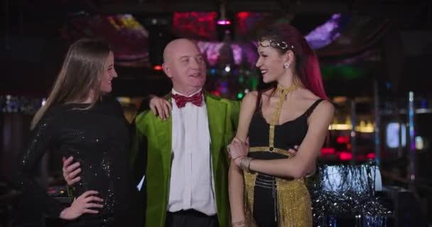 Portrét veselého staršího bělocha v zelené bundě a červeném motýlku, jak stojí se dvěma mladými ženami v nočním klubu. Starší samec DJ a samice jdou tančit v diskotéce. Cinema 4k Prores Hq.