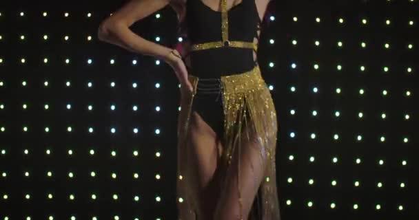 Mladý profesionální Pj tančí na pozadí černé stěny se světly v nočním klubu. Kamera se pohybuje od svůdného těla k usmívající se tváři bělocha jít tančit. Cinema 4k Prores Hq.