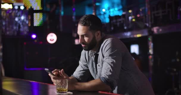 Young Middle Eastern man using smartphone and drinking alcohol next to bar counter in night club. Bored handsome guy resting alone. Cinema 4k ProRes HQ.