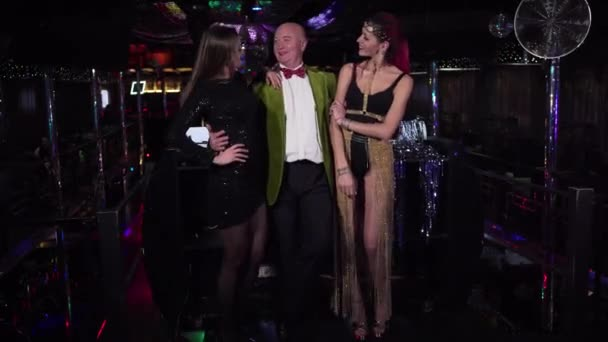 Elderly Caucasian man and two young women posing in night club. Cheerful group of people smiling and talking in disco. in front of DJ controller. Entertainment, lifestyle, club workers.