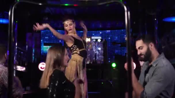 Camera approaching to young Caucasian woman in seductive dress dancing on stage in night club. Professional go go dancer working in disco surrounded by multi-racial people. Leisure, lifestyle, joy.