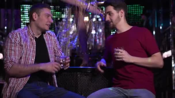 Focus changes from legs of go go dancer dancing at the background to faces of two young men drinking and talking in night club. Male friends resting in disco. Entertainment, friendship, lifestyle.