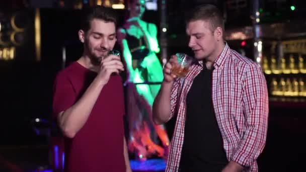 Dva mladí běloši cinkají sklenicemi a popíjejí alkohol v nočním klubu. Kamarádi odpočívající s PJ tančící v pozadí. Životní styl, volný čas, radost.