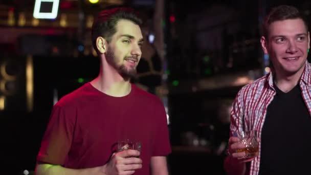 Detailní záběr dvou pohledných bělochů, jak si povídají a popíjejí alkohol v nočním klubu. Mladí pozitivní kluci odpočívají na diskotéce a jdou tancovat v pozadí. Zábava. volný čas, životní styl.