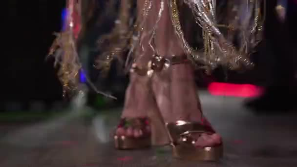 Close-up of female Caucasian feet in gold high heel shoes dancing in night club. Legs of young beautiful woman moving on stage in disco. Lifestyle, entertainment, leisure.