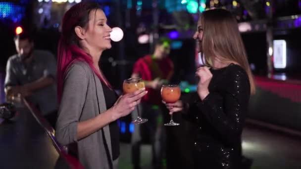 Két fiatal kaukázusi nő táncol a bárpultnál, mint jóképű közel-keleti férfi, aki piával jön. Pozitív emberek csörömpölnek és beszélgetnek az éjszakai klubban. Flört, szabadidő, életmód.