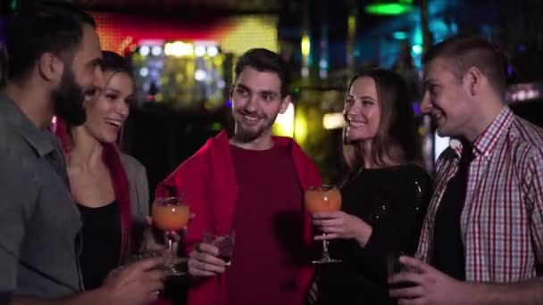 Camera approaching to group of multiethnic friends clinking glasses in night club and smiling. Positive young men and women hanging out in the evening. Lifestyle, leisure, happiness.