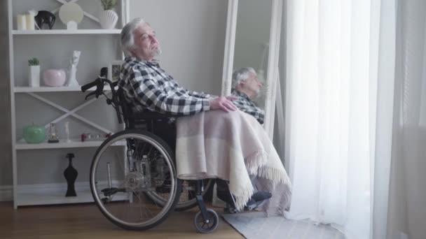 Az érett fehér hajú férfi oldalnézete, aki tolószékben ül és gondolkodik. Magányos, idős férfi, aki egyedül tölti a napot otthon. Idősek, nyugdíjasok, fogyatékkal élők.