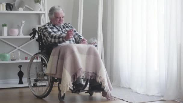 Hosszú lövés, ideges, öreg, kaukázusi fogyatékos férfi, aki fájdalmas térden veri az öklét. Idős beteg nyugdíjas, aki tolószékben ül. Betegség, fogyatékosság, sérülés, bénulás.