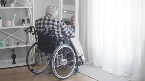 Visszapillantás az érett, tolószékes fehér férfi tükörképére. Szomorú, idős nyugdíjas, aki egyedül tölti a napot otthon. Emlékek, öregedés, nyugdíjazás, életmód.