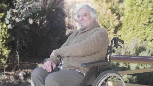 Portrait of smiling old Caucasian disabled man sitting on wheelchair and looking away. Elderly retiree in warm clothes spending sunny day outdoors. Lifestyle, happiness, enjoyment, disability.
