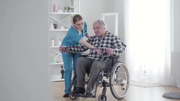 Nagy valószínűséggel koncentrált kaukázusi nő segít az öregnek megnyújtani a gumiszalagot. Időskorú nyugdíjas, aki rokkantsági segédeszköz segítségével gyakorol az idősek otthonában. Rehabilitáció, fizikoterápia.