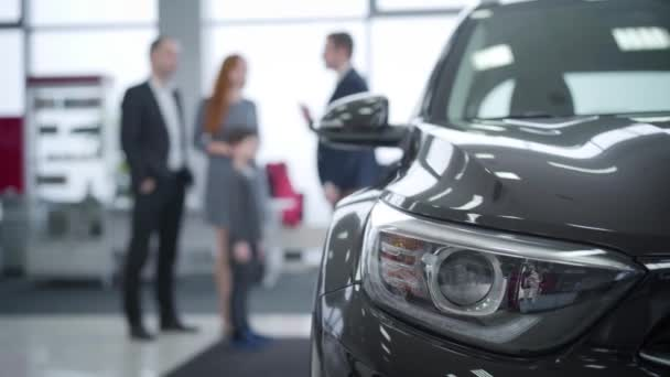 Close-up of car headlamp with blurred people talking at the background. Caucasian dealer consulting family in car dealership. Auto industry, trading, purchasing.