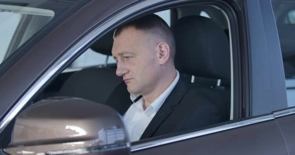 Portrait of concentrated Caucasian young man sitting on drivers seat and examining car interiors. Successful confident businessman choosing vehicle in dealership. Cinema 4k ProRes HQ.