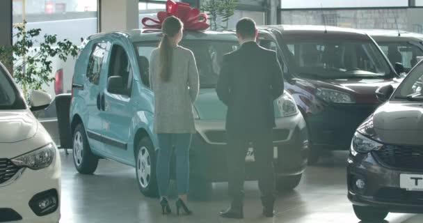 Wide shot of man and woman standing in dealership in front of aquamarine car. Back view of trader and client discussing purchase of vehicle in showroom. Cinema 4k ProRes HQ.
