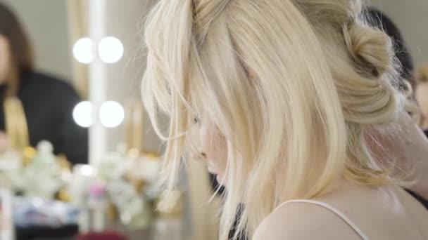 Detailní záběr na blond mladou ženu sedící v salonu krásy. Krásná bohatá běloška dělá účes. Stylista pracující s klientem. Styl, móda, krása. Zpomalený pohyb.