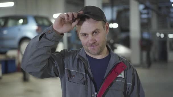 Detailní záběr dospělého bělošského údržbáře, jak si sundává víčko a rukou si otírá čelo. Usmívající se samec automechanik pózující v opravně aut. Muž pracující na čerpací stanici.