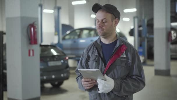 Felnőtt profi kaukázusi autószerelő néz körül a javítóműhelyben. Egy magabiztos férfi táblagépet tart az autók közötti benzinkútnál. Autóipar, hangolás, foglalkozás.