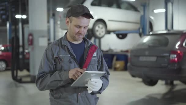 Magabiztos fehér férfi, aki táblagépet használ, és mutogatja a hüvelykujját a kamera előtt az autószerelő műhelyben. Pozitív férfi autószerelő, aki az autószerelő állomáson dolgozik. Ipar, életmód, munka.