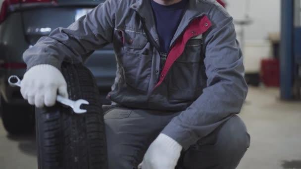Nerozpoznatelný běloch v pracovním oděvu sedí s kolem auta a klíčem a ukazuje palec nahoru. Muž automechanik pózující v autoopravně. Životní styl, zaměstnání, automobilový průmysl, profese.