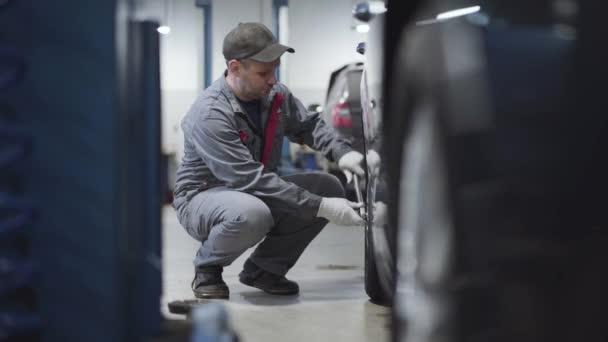 Hosszú lövés, felnőtt kaukázusi férfi, aki meghúzza a csavarokat a volánon. Oldalnézet portré karbantartó mérnök munkaruha dolgozik töltőállomás. Ipar, életmód, munka, foglalkozás.