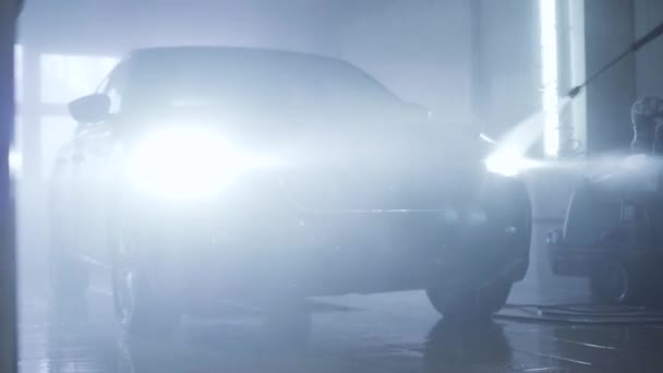 Járműmosás bekapcsolt fényszóróval az autószerelő műhelyben. Gépkocsi tisztítása kézi nagynyomású berendezéssel. Szolgáltatás, autóipar, vízpermetezés.