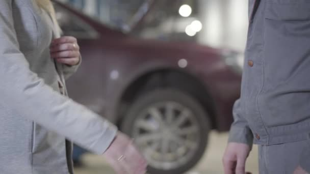 Detailní záběr běru bělošky a muže, jak si potřásají rukou v opravně aut. Úspěšná podnikatelka a profesionální údržbářka uzavírající obchod na čerpací stanici. Pojištění, údržba, podání ruky.