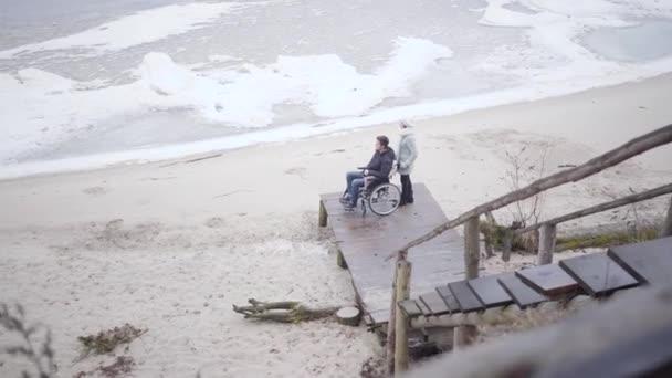 Extreme Weitschussaufnahme einer kaukasischen Frau im Rollstuhl mit einem verkrüppelten Jungen. Draufsicht auf behinderte junge Mann und seine Mutter oder ungültige Ausschreibung stehen auf Seebrücke und Blick auf Fluss.