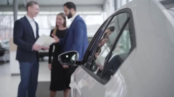 Sikeres közel-keleti üzletember és kereskedő kezet fog a bemutatóteremben. Gazdag ügyfél járművet vesz fehér feleséggel a kereskedésben. Középpontjában a fehér autó az előtérben.
