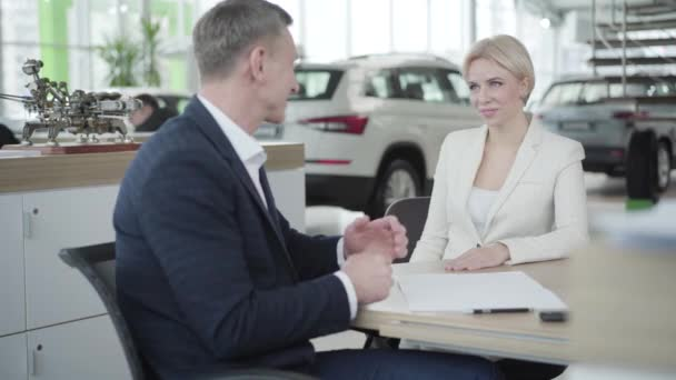Young smiling Caucasian woman passing business card to adult man in car dealership. Trader and client shaking hands in showroom. Automotive industry, luxury, success.