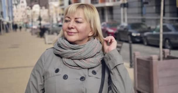 Portrét elegantní starší bělošky stojící na ulici v slunečný podzimní den. Šťastná dospělá žena si užívá důchod venku. Důchodce na penzi. Cinema 4k Prores Hq.