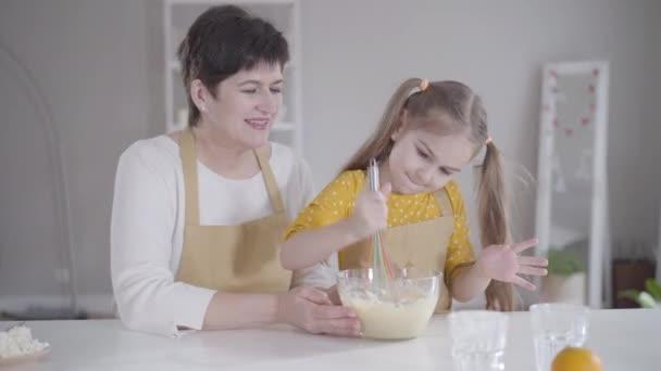 Malá hezká holčička sedící s babičkou v kuchyni a mlátící vajíčka moukou. Roztomilé bělošské dítě pomáhá vařit chutné palačinky v úterý Shrove. Pečení, životní styl, Shrovetide.