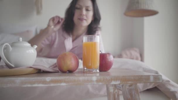 Homályos kaukázusi nő friss almát vesz le az asztalról, és otthon mászik el az ágyon. Boldog mosolygós hölgy, aki bio gyümölcsöt eszik reggel. Wellness, életmód, öröm.